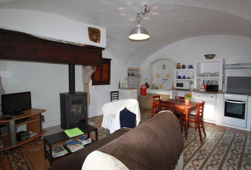 Cuisine et coin salon dans la pièce à vivre voûtée avec carreaux ciment